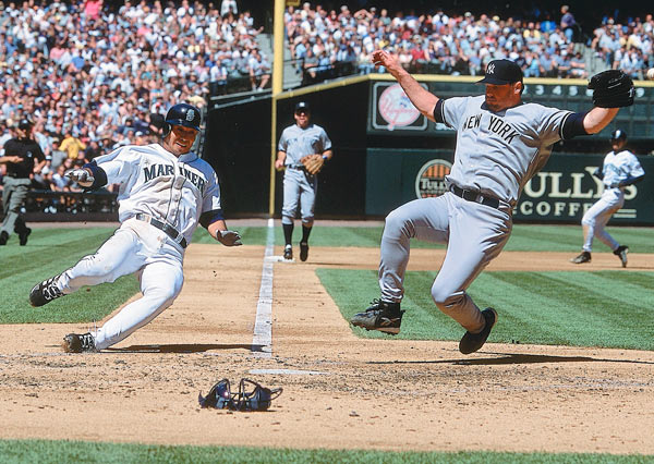 Clemens slides home to cover the plate as Seattle's Carlos Guillen tries to score during a Yankees-Mariners game at Safeco Field in 2001.