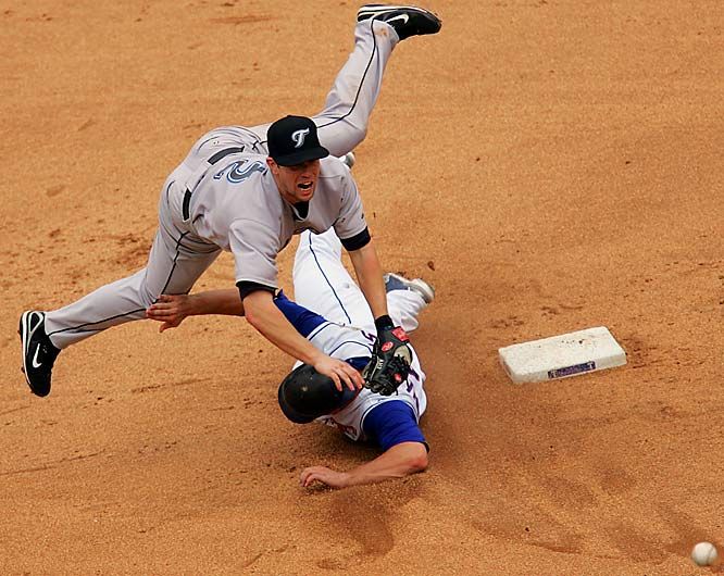 Blue Jays second baseman Aaron Hill avoids the slide by Brad Wilkerson, turning a double play in the seventh inning on Sunday. The Rangers beat the Jays 3-2.