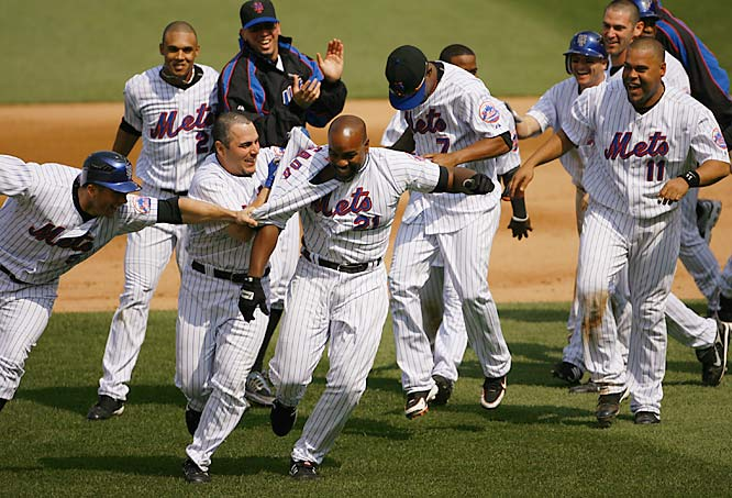 Carlos Delgado is mobbed after his two-run single capped a five-run rally in the bottom of the ninth, giving the Mets a 6-5 win over the Cubs on May 17.