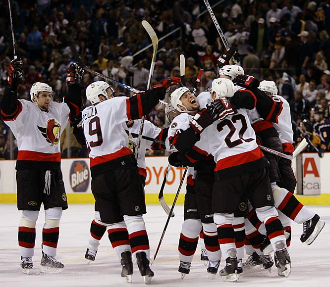 A bouncing shot by defenseman Joe Corvo, center, skipped in at 4:58 of the second overtime, setting off a celebration.