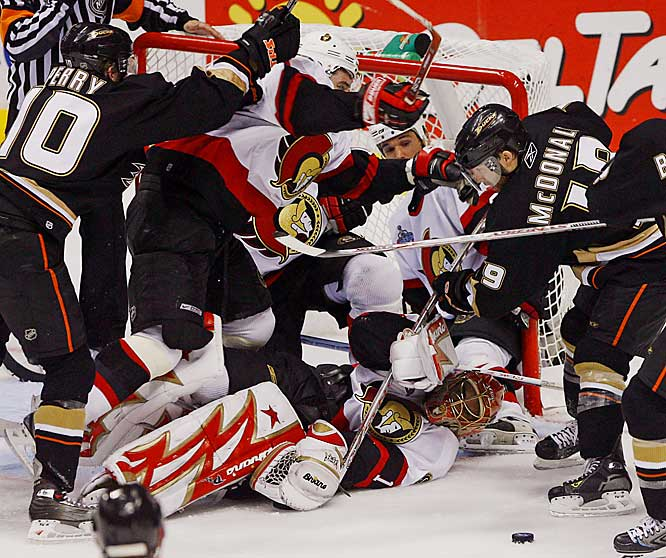 Ottawa goalie Ray Emery is overwhelmed by a crowd of players during the third period. The Ducks outshot the Senators 14-7 in the final period, scoring twice on Emery for the victory.
