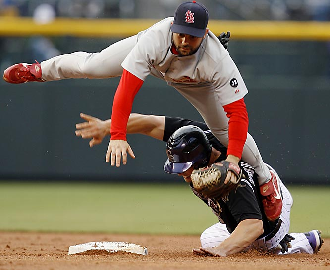 Cardinals shortstop Aaron Miles flies over the Rockies' Matt Holiday after forcing him out at second and making the throw to first for a double play to end the first inning May 31 at Coors Field. St. Louis won 7-3.