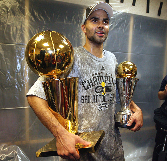 Tony Parker cradles the Larry O'Brien trophy and his Finals MVP trophy in the locker room.