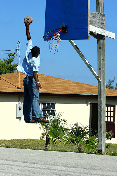 A basketball player on Cat Island in the Bahamas shows why the rim on a local court is coming off the backboard.