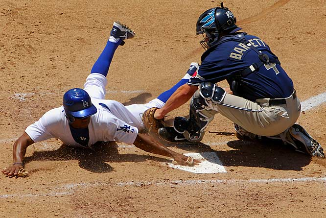 Juan Pierre slides home safely beneath the tag of Padres catcher Michael Barrett in the third inning Sunday at Dodger Stadium. The Dodgers won 5-0.