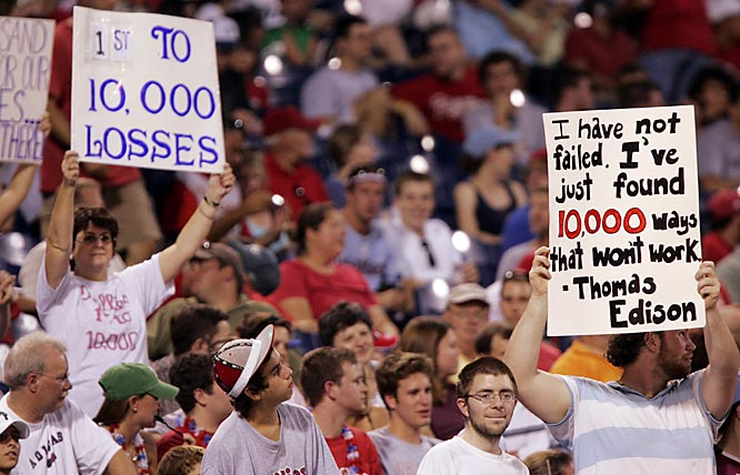 Phillies fans hold up signs as their team loses its 10,000th game in franchise history Sunday night against the Cardinals.