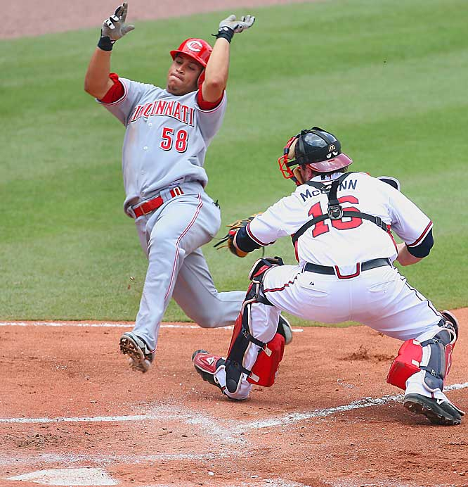 Cincinnati's Pedro Lopez is tagged out by Braves catcher Brian McCann as he tries to score on a double by Aaron Harang in the fifth inning July 18 at Turner Field. The Reds won the game 5-4 in 15 innings.