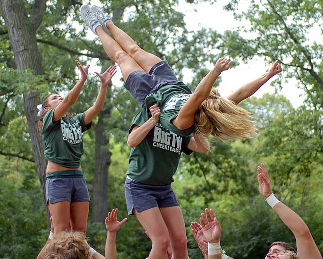 The Michigan State squad executes a single somersault entrance into a flatback during team elite stunting practice.