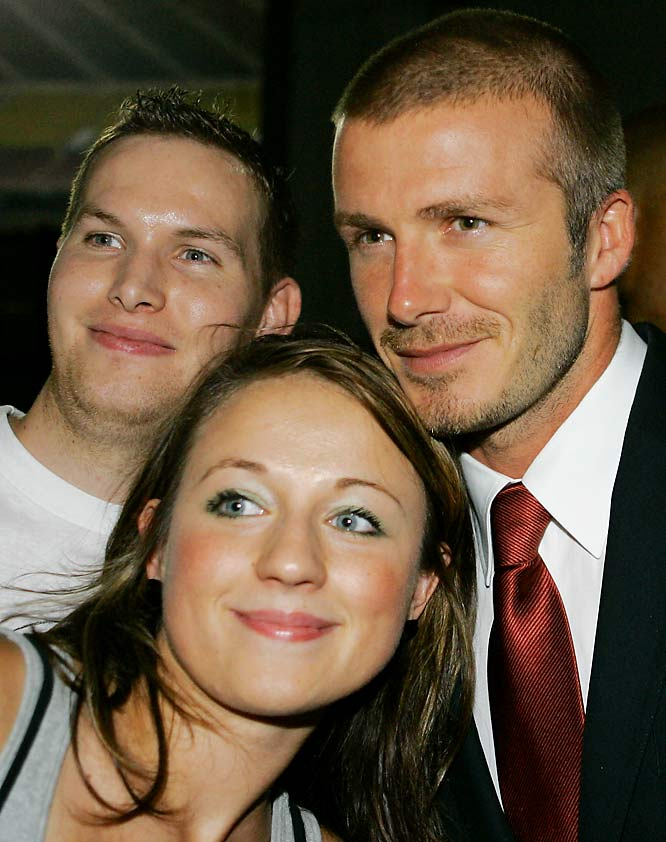 We love when guys awkwardly try to get in a picture, like the dude on the left who clearly looks like a third wheel between David Beckham and his cute fan.