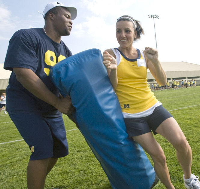 Defensive end Adam Patterson works with camper Janeese Mackey during the Michigan Womens Football Academy, one of the Wolverines summer activities that benefit the Coach Carr Cancer Fund.