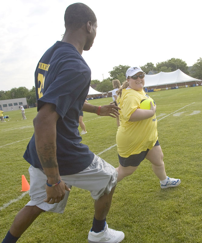Wide receiver Mario Manningham and the Wolverines put campers like Elizabeth Von Allmen through drills in an event that ended with a scrimmage in Michigan Stadium.