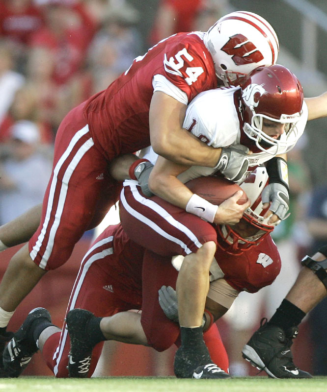Mike Newkirk (54) sacked Washington State quarterback Alex Brink as the Badgers bottled up the Cougars signal-caller in the second half to take the opener.