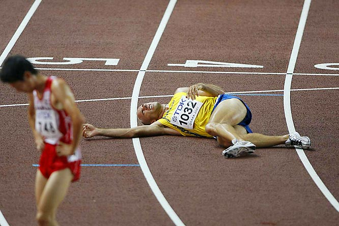 Sweden's Erik Sjoqvist collapses at the finish line after failing to qualify in the first heat of the Men's 5,000-m.