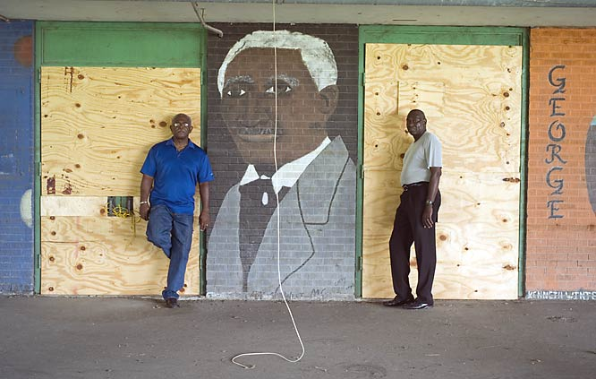 Ron Gearing (left) and Walter Tillman, standing here outside of Carver High, are both athletic directors in the New Orleans area. They're big propopents of rebuilding sports facilities because evidence shows that kids who participate in extracurricular activities graduate at a higher rate.