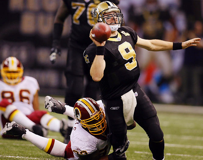 Drew Brees is tripped up by Washington's Phillip Daniels in a 16-10 loss.