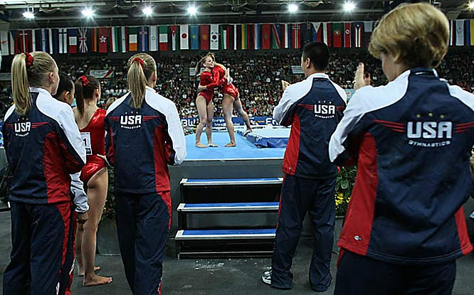 The team applauds after Shawn Johnson finishes with a team-high 15.375 on the mat.