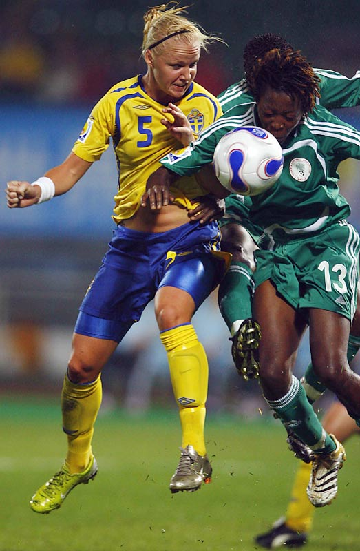 Sweden's Caroline Seger (5) challenges Nigeria's Christine George for the ball.  Seger hoisted a header over the bar in the 57th minute.