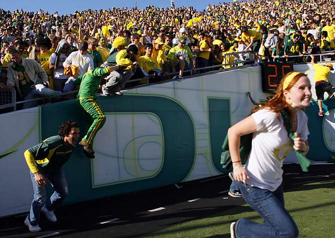 Oregon fans rush the field after the Ducks' victory over  USC.