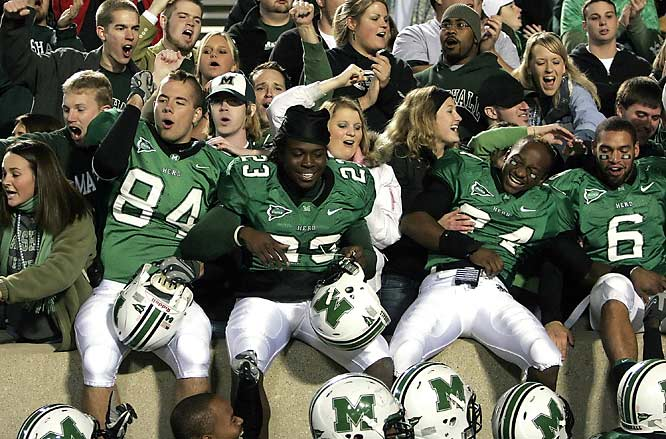 Marshall players Hunter Hamrick (84), Bryant Milligan (23), Emmanuel Spann (24) and Shawn Lauzon (6) celebrate the team's first victory of the season, a 34-21 triumph over Rice.