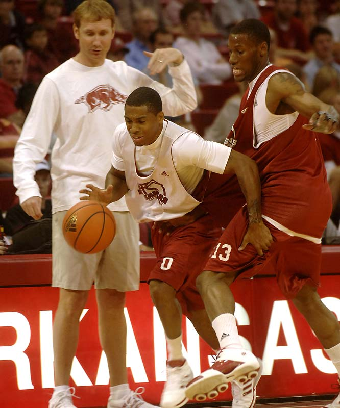 Arkansas head basketball coach John Pelphrey watches as Gary Ervin, center, drives around Sonny Weems  during a red/white basketball scrimmage