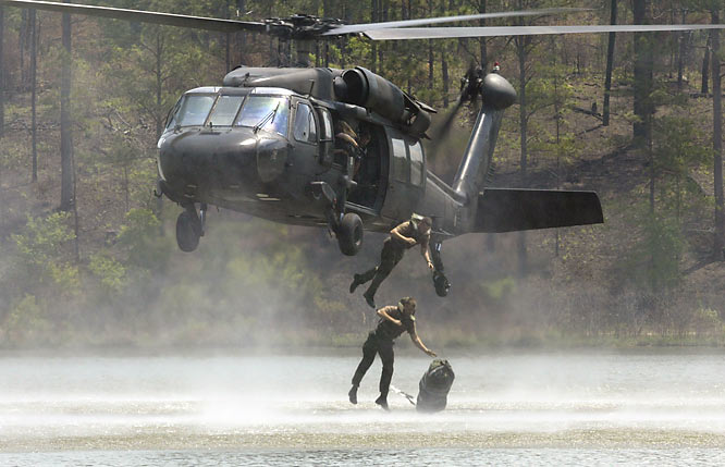 Unquestionably one of the coolest assignments I have ever done. The Army's Best Ranger competition is held annually at Ft. Benning, Ga, and is a grueling 60-hour, non-stop, two-man team competition. Here, the team drops from a helicopter into a lake with full gear. The men swim to shore with the gear attached, then lift the gear and carry it to a designated location. I was standing on a sand bar type island in the lake as the men jumped from a hovering helicopter. These men are truly amazing! <br><br>Shot with: Canon EOS-1D, EF 300mm f/2.8L IS USM, shot at 1/320 f/13.0