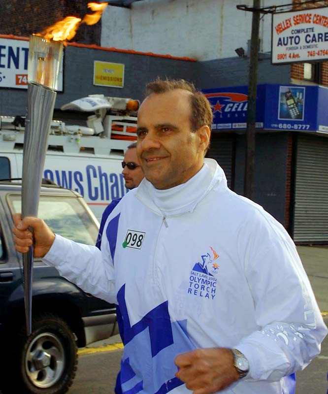 Torchbearer Torre carries the Olympic Flame during the 2002 Salt Lake Olympic Torch Relay in Brooklyn, N.Y.