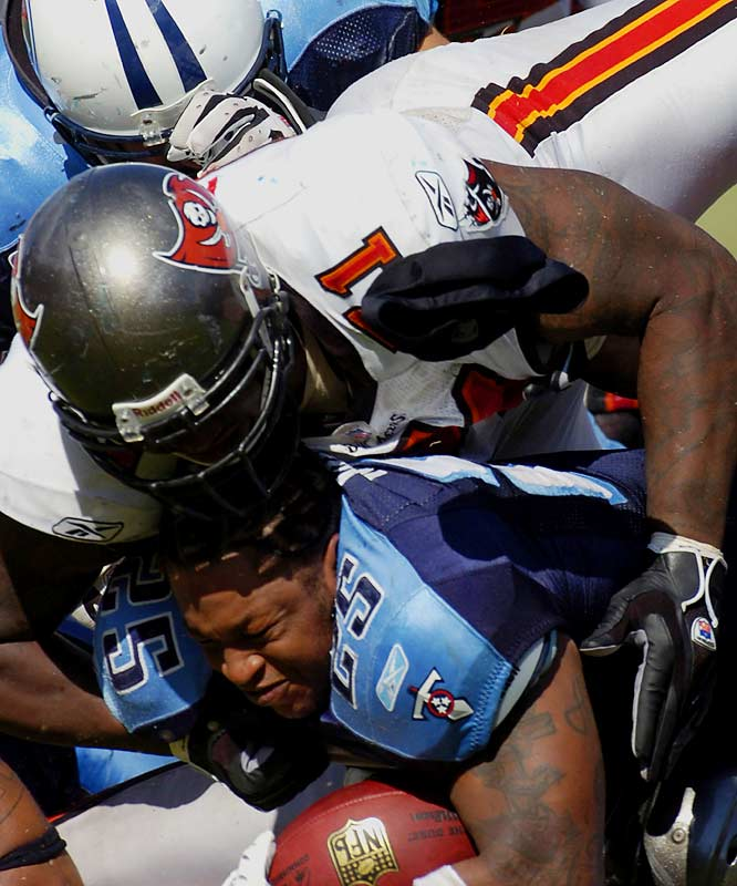 Titans' running back LenDale White loses his helmet during a tackle and pileup.