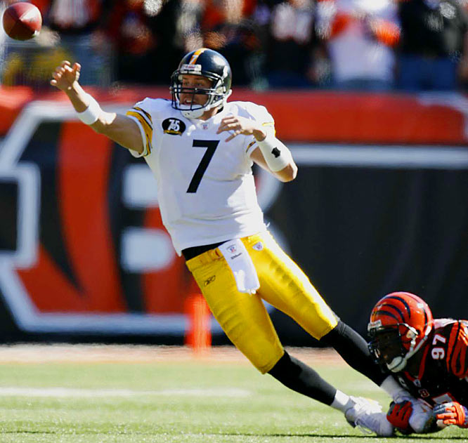 With the Bengals' John Thornton pulling him down by the ankle, Ben Roethlisberger maintains great balance to complete a pass to Santonio Holmes for a first down early in the second quarter.