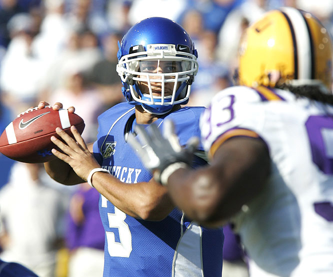 Andre Woodson threw for 250 yards and three touchdowns, including a 7-yard strike to Steve Johnson in the third overtime, as the Wildcats beat a No. 1 ranked team for the first time in 43 years.