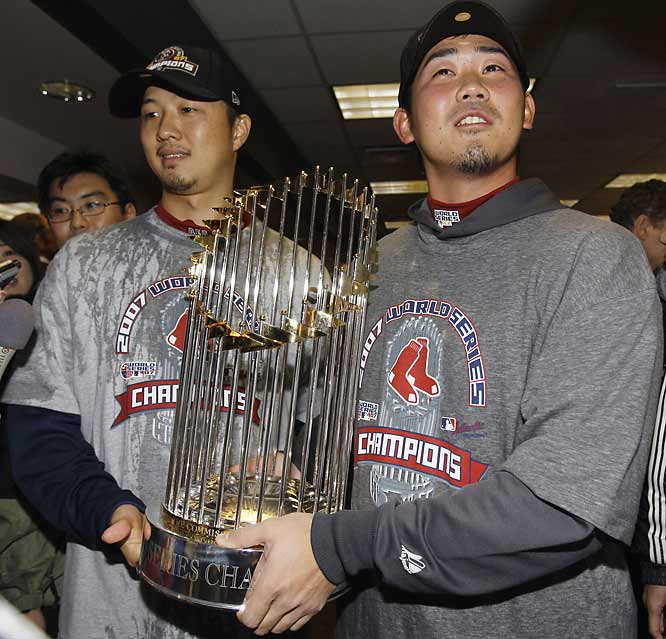 After lights-out performances in the postseason, Daisuke Matsuzaka and Hideki Okajima hold up their first World Series championship trophy.
