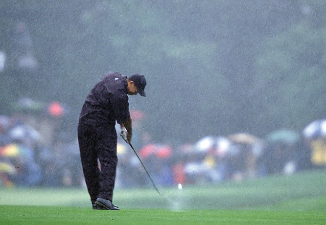 It's no fun trying to keep camera equipment dry while working in the rain, but poor conditions can enhance a picture, as the rain did with this photo of Tiger Woods at the 2002 U.S. Open at Bethpage Black. Just as is the case with golfers, we have to get inside if lightning strikes -- camera equipment can act like a lightning rod.<br><br>Shot with: Canon EOS-1v (film camera), EF 600mm f/4.0L IS USM, shot at 1/1000 f/4.0
