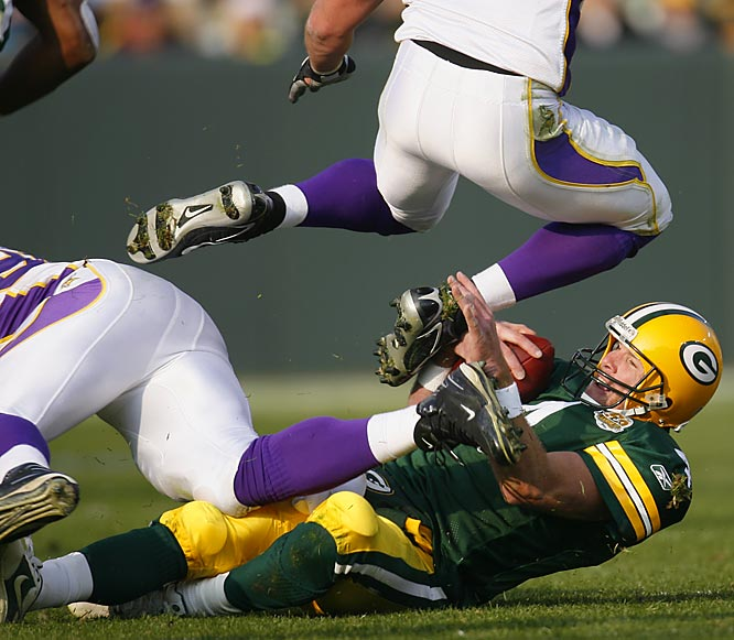 Brett Favre takes a late hit from Vikings defensive end Kenechi Udeze, left, as he slides and attempts to avoid a leaping Chad Greenway for a 1-yard gain in the third quarter.  Udeze was called for a personal foul.