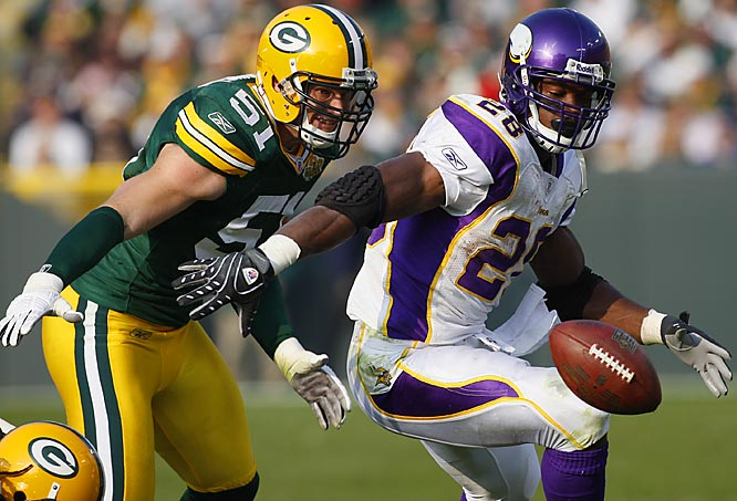 Adrian Peterson recovers his own fumble, forced by Packers linebacker Brady Poppinga, left, in the third quarter. The Packers held Peterson to just 45 yards on the ground.
