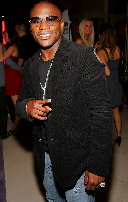Boxer Floyd Mayweather Jr. points with his unadorned hand at a housewarming party for Gavin Maloof.