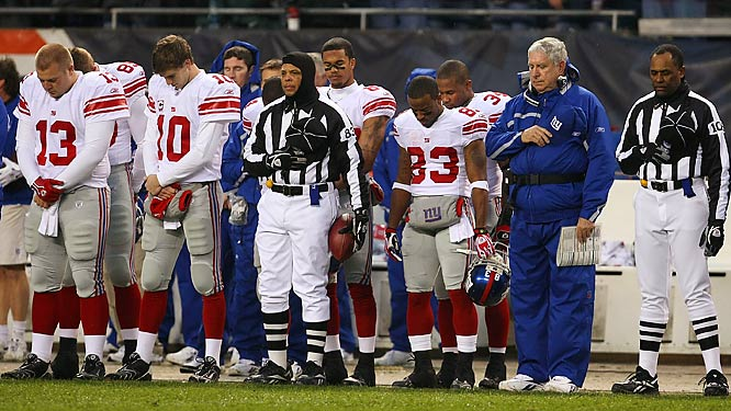 Referees, coaches, and members of the Giants, including Jared Lorenzen (13), Eli Manning (10) and Sinorice Moss (83) pause for a moment of silence.