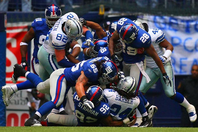 The Giants' defense, led by Michael Strahan (92) and Kawika Mitchell (55), stopping running back Marion Barber III.