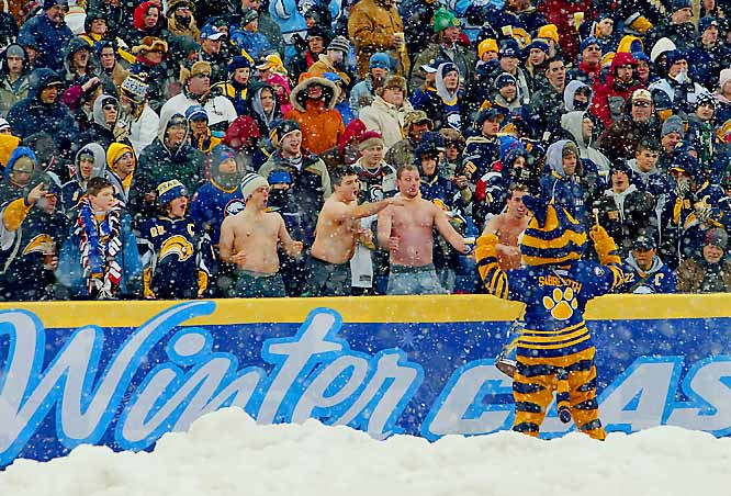Fans, both shirtless and dressed in layers, cheer with Sabres mascot Sabretooth.