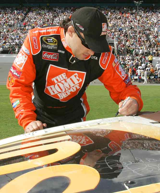 Tony Stewart, NASCAR's points champ in 2002 and '05, autographs the vehicle of three-time Daytona 500 winner Dale Jarrett, who will be retiring this year. Stewart ended up in third place, 13 slots higher than Jarrett.