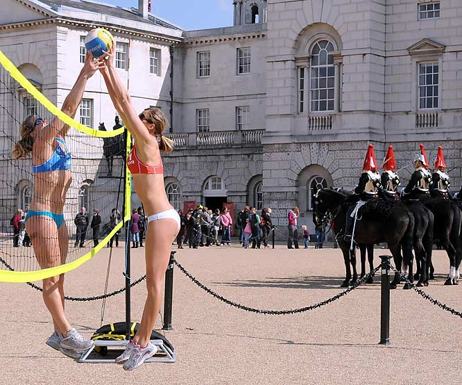 British beach volleyball Olympic hopefuls, Lucy Boulton, left, and Denise Johns, practice as the Household Cavalry change the guard on Horse Guards Parade in central London on Thursday. Horse Guards Parade will be the venue for the beach volleyball competition for the 2012 Olympic Games in London.
