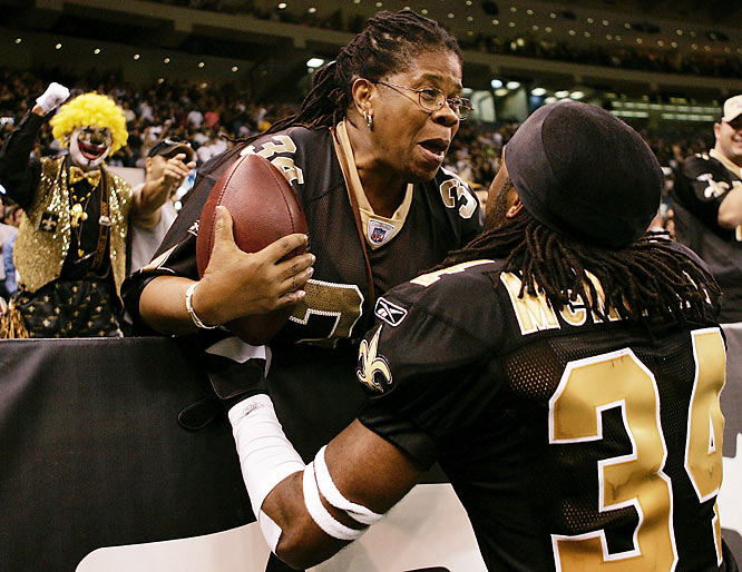 After an interception and return for a touchdown, New Orleans Saints cornerback Mike McKenzie hands the football to his mother, Frances.