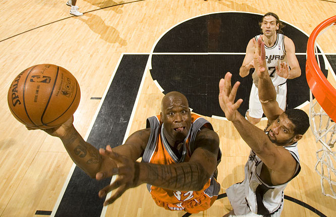 The Suns' Shaquille O'Neal goes up for a shot against Tim Duncan.