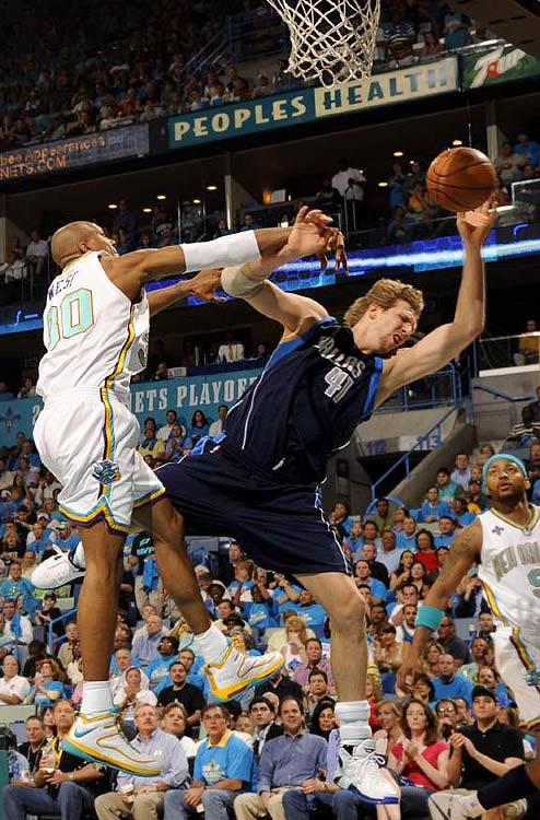 The Mavericks' Dirk Nowitzki is fouled by David West of the Hornets on a hard drive through the lane.
