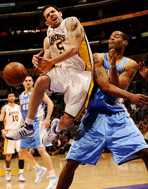 Lakers guard Jordan Farmar loses control of the ball as Marcus Camby looks on.