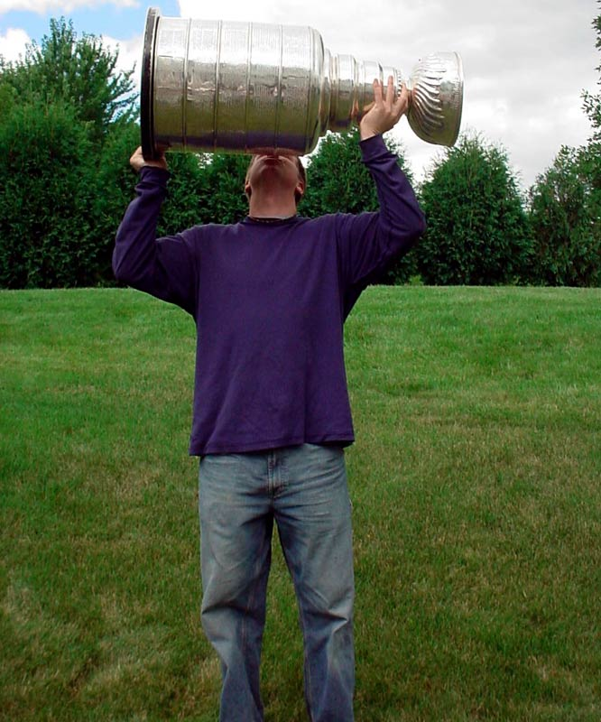 """Here's a photo of Andy Disch hoisting the Stanley Cup on what appears to be a picturesque scene. """"I have won the cup multiple times on Sega and Playstation for a couple different teams, and even once I got to hold the REAL thing. Don't worry it never touched my lips! I kept the hockey players tradition of not kissing it until I actually win it."""""""