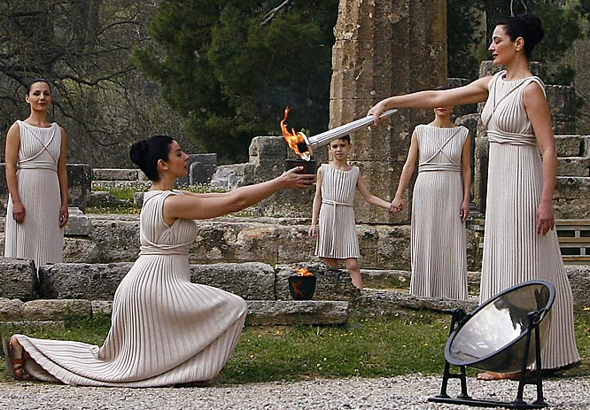 "Portraying the ""High Priestess"" of ancient Greece, actress Maria Nafpliotou lights the flame by a reflection of sunlight on a parabolic mirror before sending it on. But the Olympic Torch relay hasn't been as serene as the Olympiad enactment shows. Those opposed to China's policies in Tibet and its overall human rights record have protested all along the torch's path."