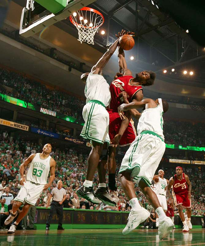 Wallace snatching one of his four rebounds as Garnett contests.