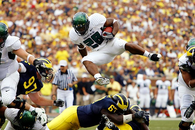 Running back Jonathan Stewart leaps over a Michigan defender on his way to 111 yards and a 39-7 Oregon win.