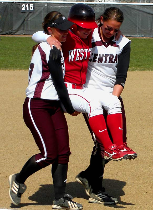 Western Oregon's Sara Tucholsky is carried around the bases by Central Washington's Liz Wallace and Mallory Holtman after injuring her knee while rounding first base following her first-career home run.