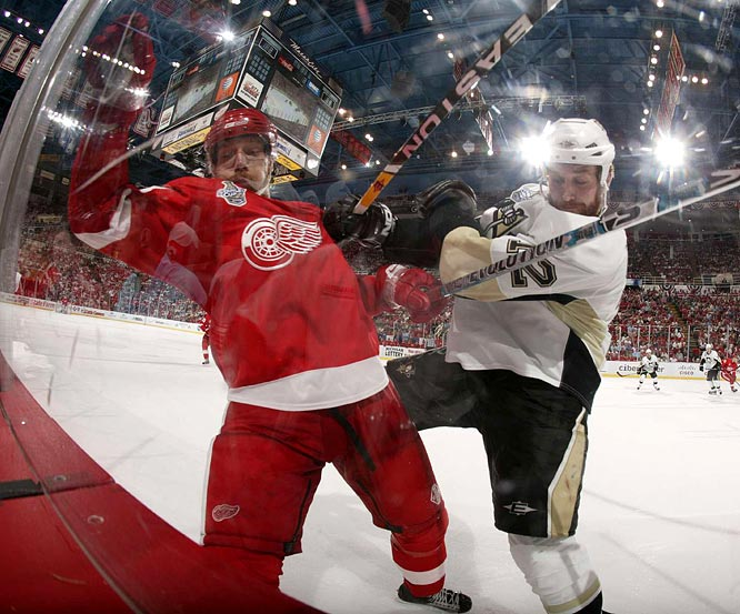 Red Wings Mikael Samuelsson, a former Penguin, is checked into the boards by Ryan Malone as the two teams begin a grueling, wearying battle that lasts into a third overtime period.