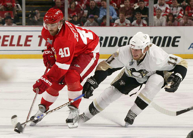 """Conn Smythe candidate Henrik Zetterberg tries to control the puck while being checked by Jordan Staal. Zetterberg set up the game-tying goal by Pavel Datsyuk early in the third period, inciting chants of """"We want the Cup!"""""""